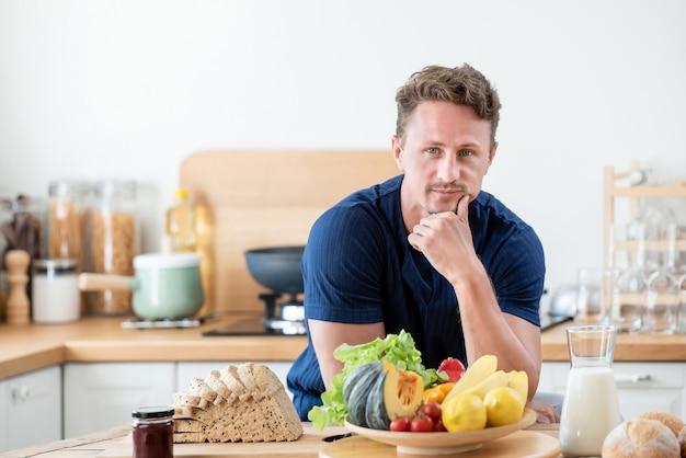 Homem saudável no kitcken com comida saudável em cima da mesa