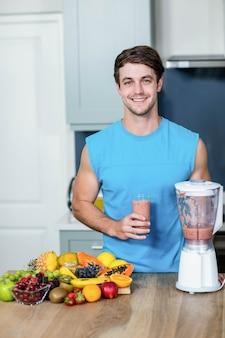 Homem saudável preparando um smoothie na cozinha