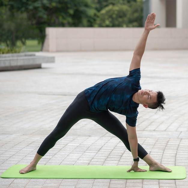 Homem se alongando enquanto faz ioga ao ar livre