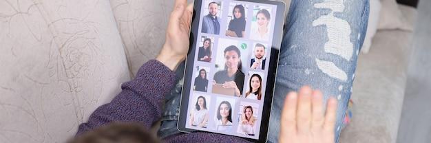 Homem se comunicando com muitos colegas em um tablet digital em casa