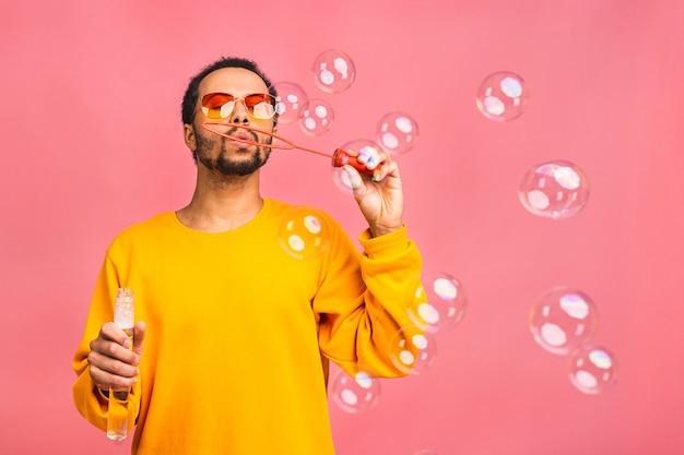 Homem se diverte com bolhas de sabão. isolado sobre rosa