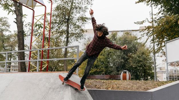 Homem se divertindo com o skate no parque da cidade
