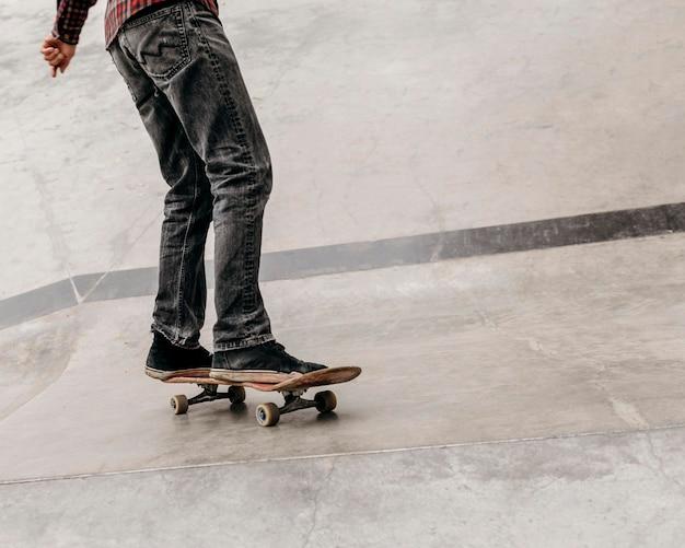 Homem se divertindo com skate ao ar livre no parque da cidade