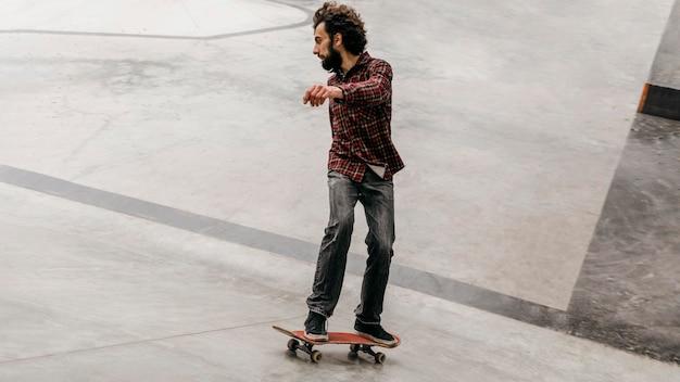 Homem se divertindo com skate ao ar livre no parque
