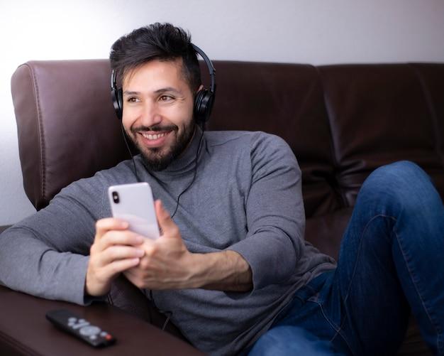 Homem se divertindo olhando para smartphone com fones de ouvido