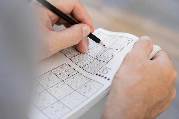 Homem se divertindo sozinho em um jogo de sudoku no papel