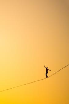 Homem se equilibrando em uma corda contra o céu
