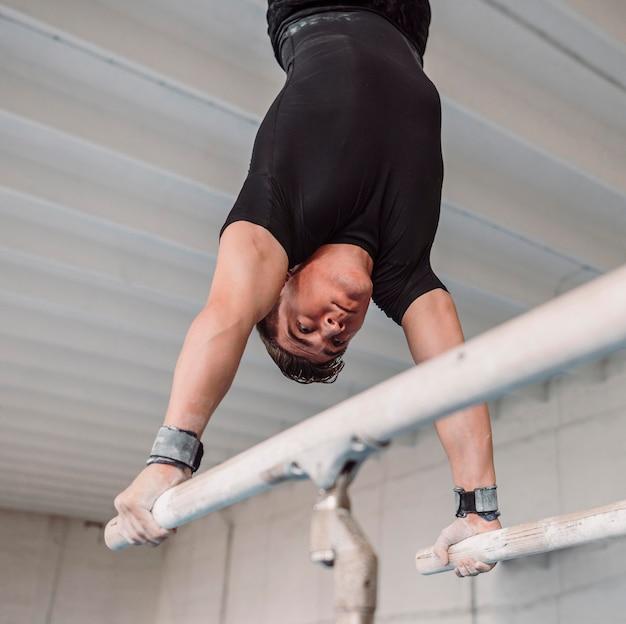 Homem se exercitando em barras paralelas
