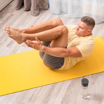 Homem se exercitando em casa no tatame com garrafa de água