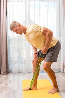 Homem se exercitando em casa usando elástico