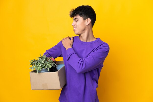Homem se mexendo enquanto apanha uma caixa cheia de coisas sofrendo de dores no ombro por ter feito esforço