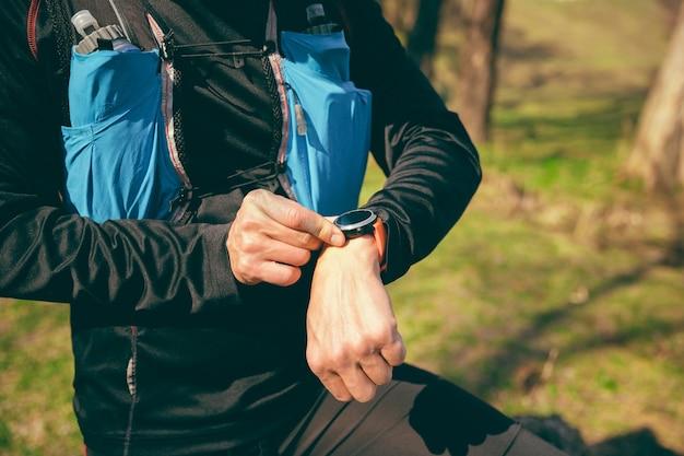 Homem se preparando para correr em um parque ou floresta contra árvores