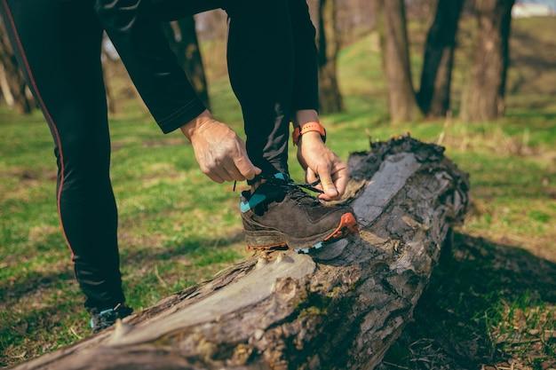 Homem se preparando para correr em um parque ou floresta contra o espaço das árvores