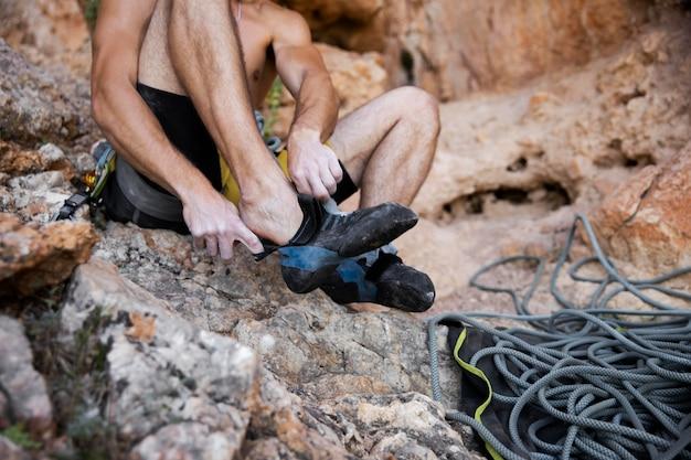 Homem se preparando para escalar uma montanha