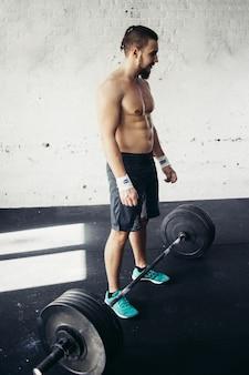 Homem se preparando para o treinamento de barra no ginásio
