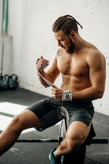 Homem se preparando para o treinamento, envolvendo as mãos com fita adesiva