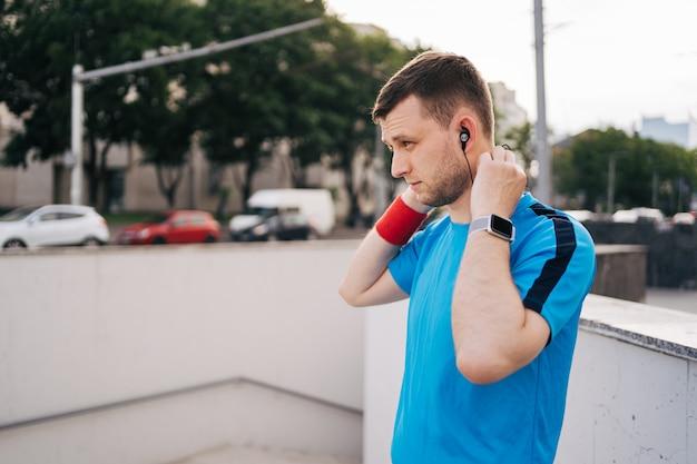 Homem se preparando treino cidade arranjando fones de ouvido