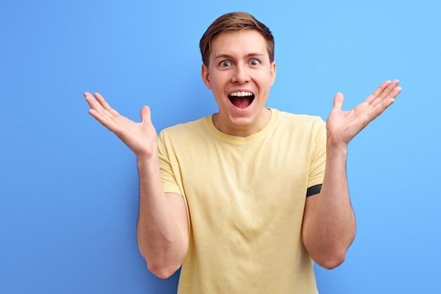 Homem se regozija e comemora a vitória em fundo azul, gesticulando positivo masculino de mente aberta, levantando as mãos e olhando para a câmera com a boca aberta, receba boas notícias