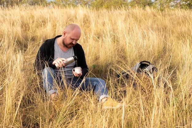 Homem se senta na grama e serve chá em uma xícara de uma garrafa térmica