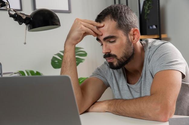 Homem se sentindo cansado enquanto trabalha em casa