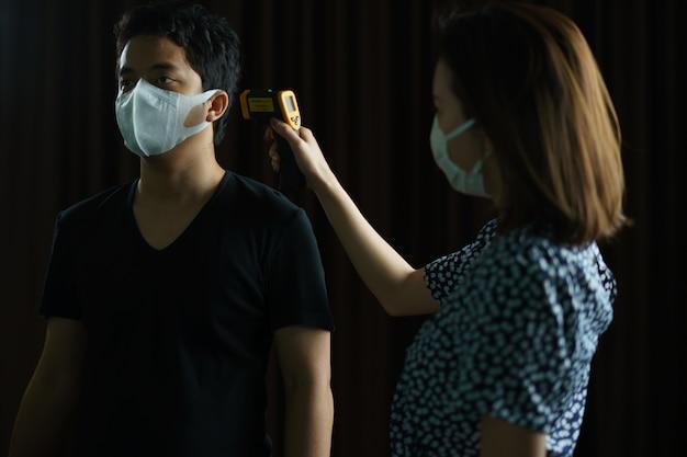 Homem se sentindo doente e vestindo máscara protetora verificada por mulher com máscara médica