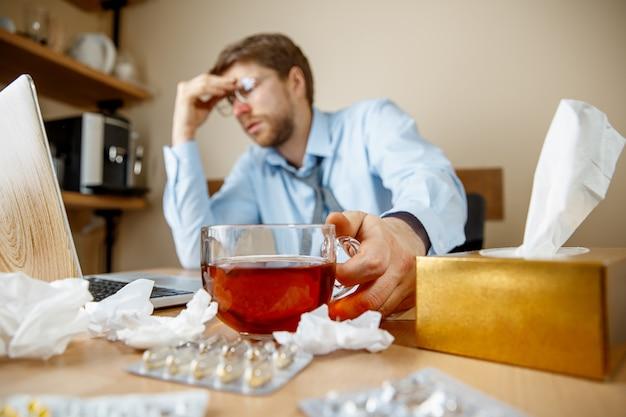 Homem se sentindo enjoado e cansado, bebendo chá