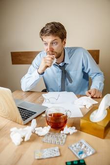 Homem se sentindo enjoado e cansado, trabalhando em casa