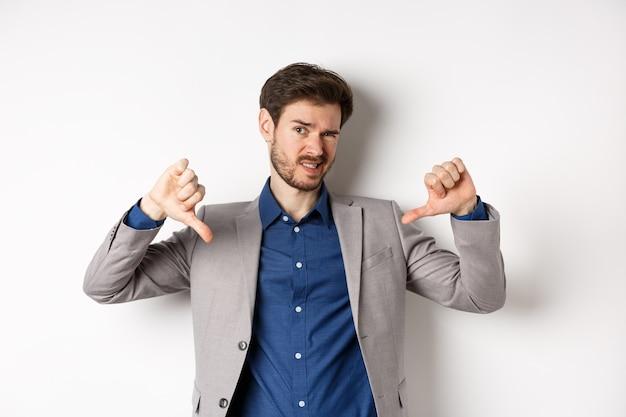 Homem se sentindo estranho mostrando os polegares para baixo e julgando algo ruim