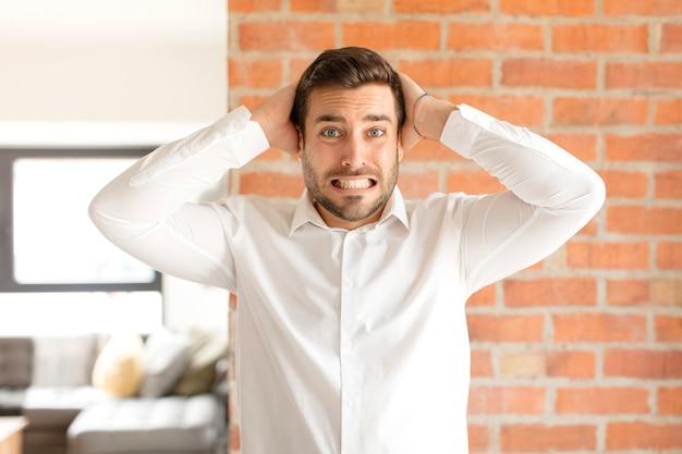 Homem se sentindo estressado, preocupado, ansioso ou com medo, com as mãos na cabeça, entrando em pânico com o erro