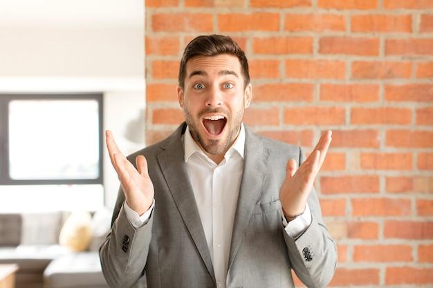 Homem se sentindo feliz, animado, surpreso ou chocado, sorrindo e surpreso com algo inacreditável