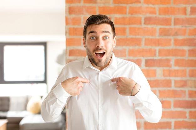 Homem se sentindo feliz, surpreso e orgulhoso, apontando para si mesmo com um olhar empolgado e surpreso