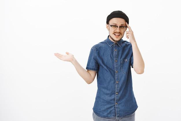 Homem se sentindo irritado cutucando a têmpora com o dedo indicador, encolhendo os ombros com a palma da mão aberta e olhando com expressão confusa e perplexa