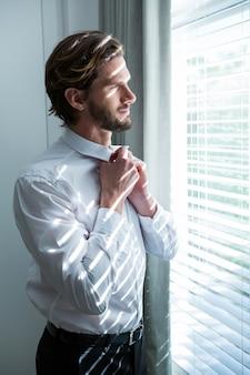Homem se vestindo enquanto olha através das cortinas da janela