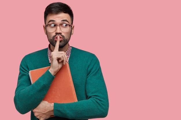 Homem secreto por fazer silêncio faz gesto de silêncio, segura um livro vermelho grosso, olha para o lado conspirando