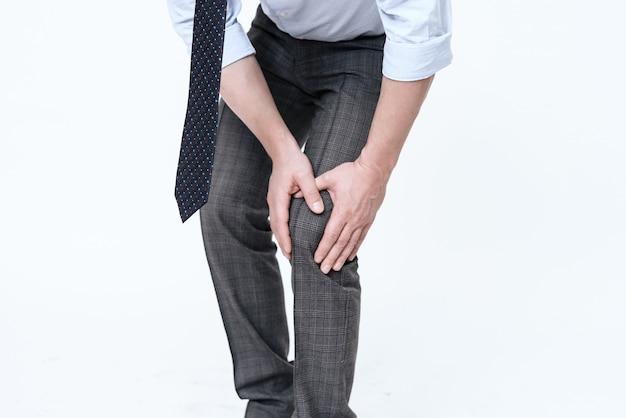 Homem segura a mão para o ponto dolorido. ele massagens.
