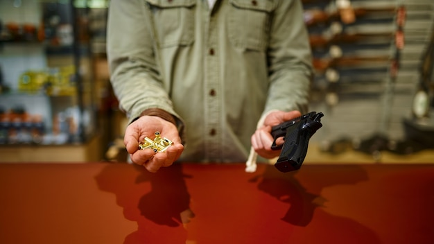 Homem segura arma e balas no balcão da loja de armas. interior da loja de armas, sortimento de munições e munições, escolha de armas de fogo, hobby de tiro e estilo de vida, autoproteção
