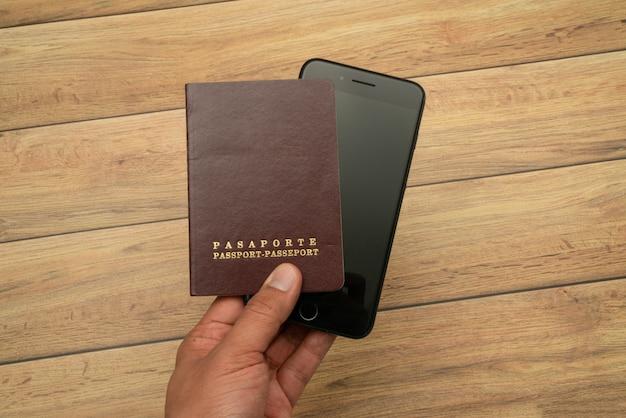 Homem segura com a mão o passaporte e smartphone, mapa do mundo. conceito de viagens