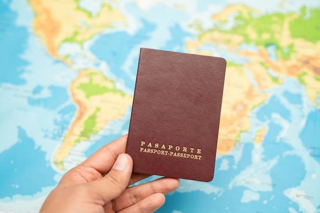 Homem segura com a mão o passaporte, mapa do mundo. conceito de viagens