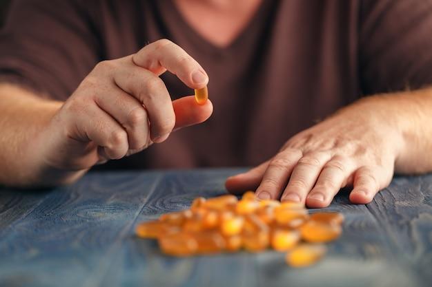Homem segura comprimidos na mão