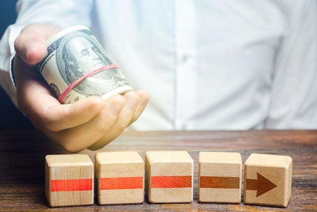 Homem segura dinheiro acima dos blocos da seta vermelha financiando e investindo na conclusão de um negócio