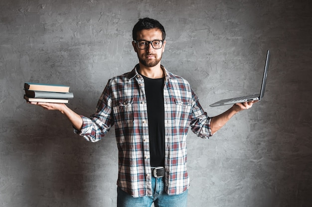 Homem segura em um livro de mão com laptop no fundo da parede cinza. educação, conhecimento, sucesso