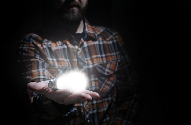Homem segura lâmpada incandescente na mão