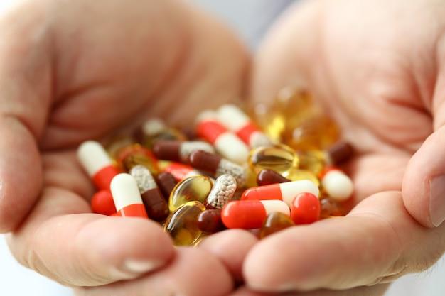 Homem segura nos braços conjunto de close-up comprimidos diferentes