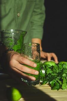 Homem segura o copo disponivel com batido de desintoxicação saudável, cozinhando com liquidificador com frutas frescas e espinafres verdes, conceito de desintoxicação de estilo de vida. conceito de desintoxicação de estilo de vida. bebidas veganas.