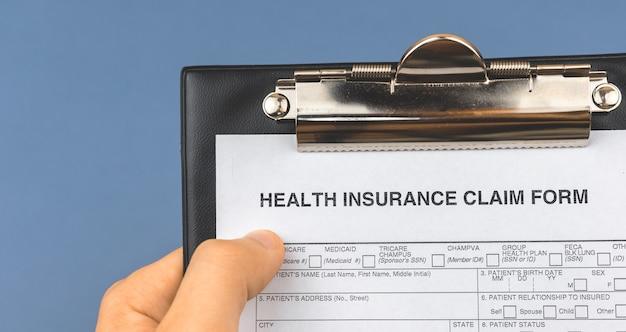 Homem segura o formulário de pedido de seguro saúde na área de transferência. bandeira. foto do conceito de documento de medicamento