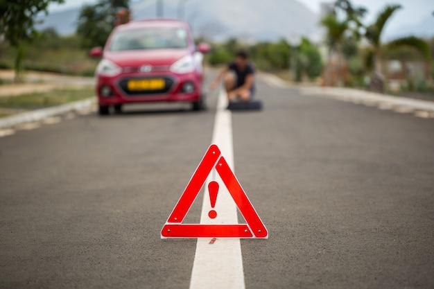 Homem segura o pneu sobressalente contra um carro avariado