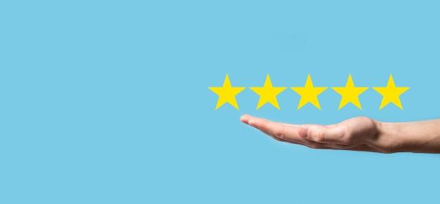 Homem segura o smartphone nas mãos e dá uma avaliação positiva, o ícone do símbolo de cinco estrelas para aumentar a avaliação do conceito da empresa na superfície azul