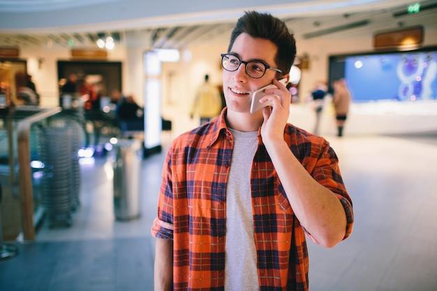Homem segura o smartphone no shopping