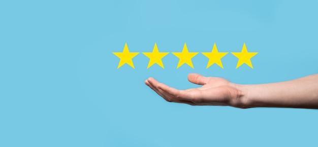 Homem segura o telefone inteligente nas mãos e dá uma avaliação positiva, o símbolo de cinco estrelas do ícone para aumentar a avaliação do conceito da empresa sobre fundo azul. pesquisa de satisfação do negócio e experiência de serviço ao cliente.