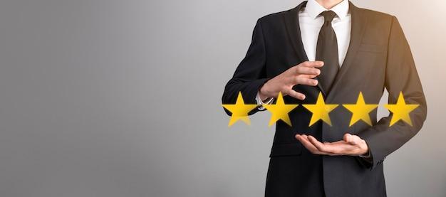 Homem segura o telefone inteligente nas mãos e dá uma avaliação positiva, o símbolo do ícone cinco estrelas para aumentar a avaliação do conceito da empresa sobre fundo azul. pesquisa de satisfação do negócio e experiência de serviço ao cliente.